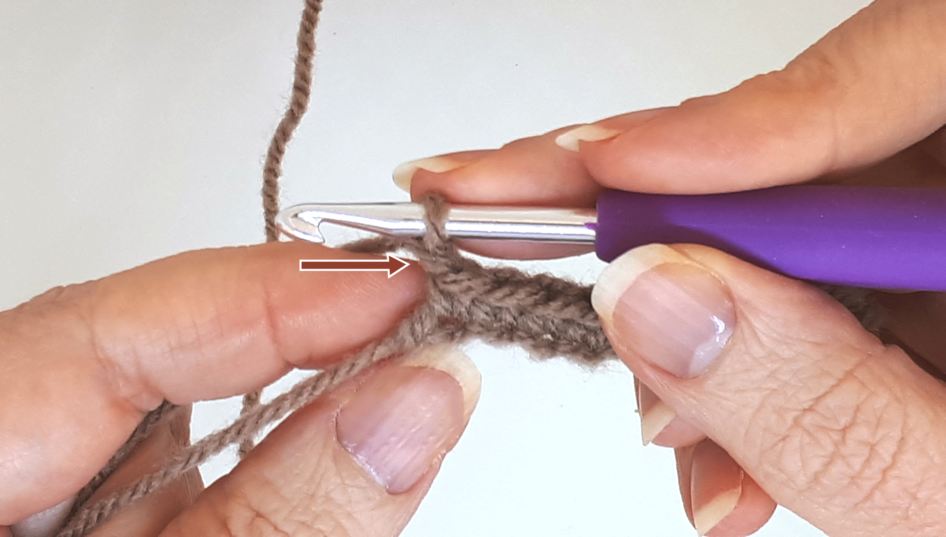 Close-up to a woman's hand crocheting with an arrow pointing to the first stitch