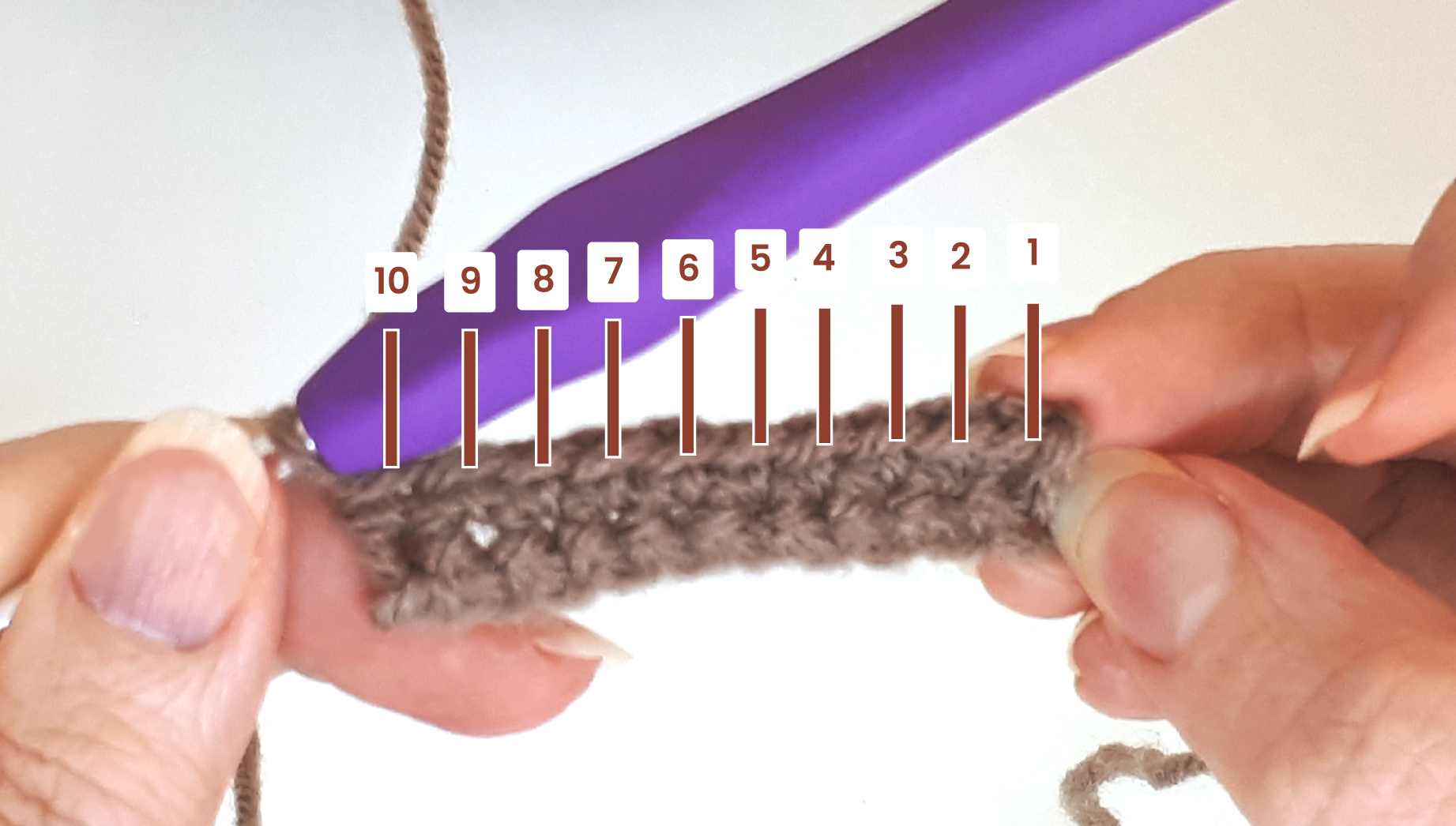 Close-up to a woman's hand showing 10 completed crochet stitches