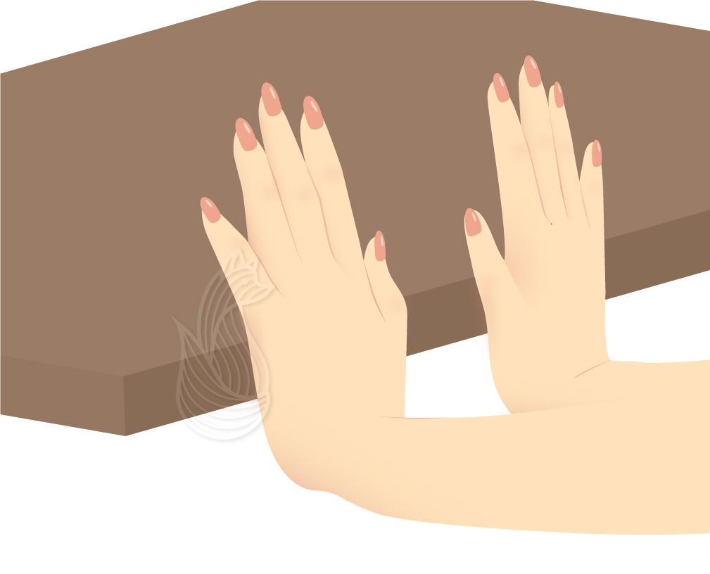 Hands with palms pushed against the edge of a brown table, doing the flexor crocheter's exercise