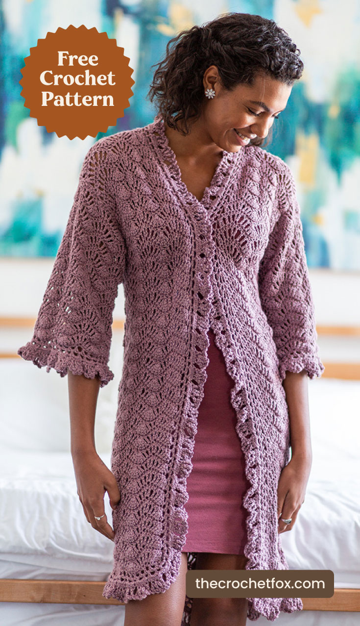 "A woman wearing a purple crochet dressing gown at the beach and text area which says ""Free Crochet Pattern, thecrochetfox.com"""