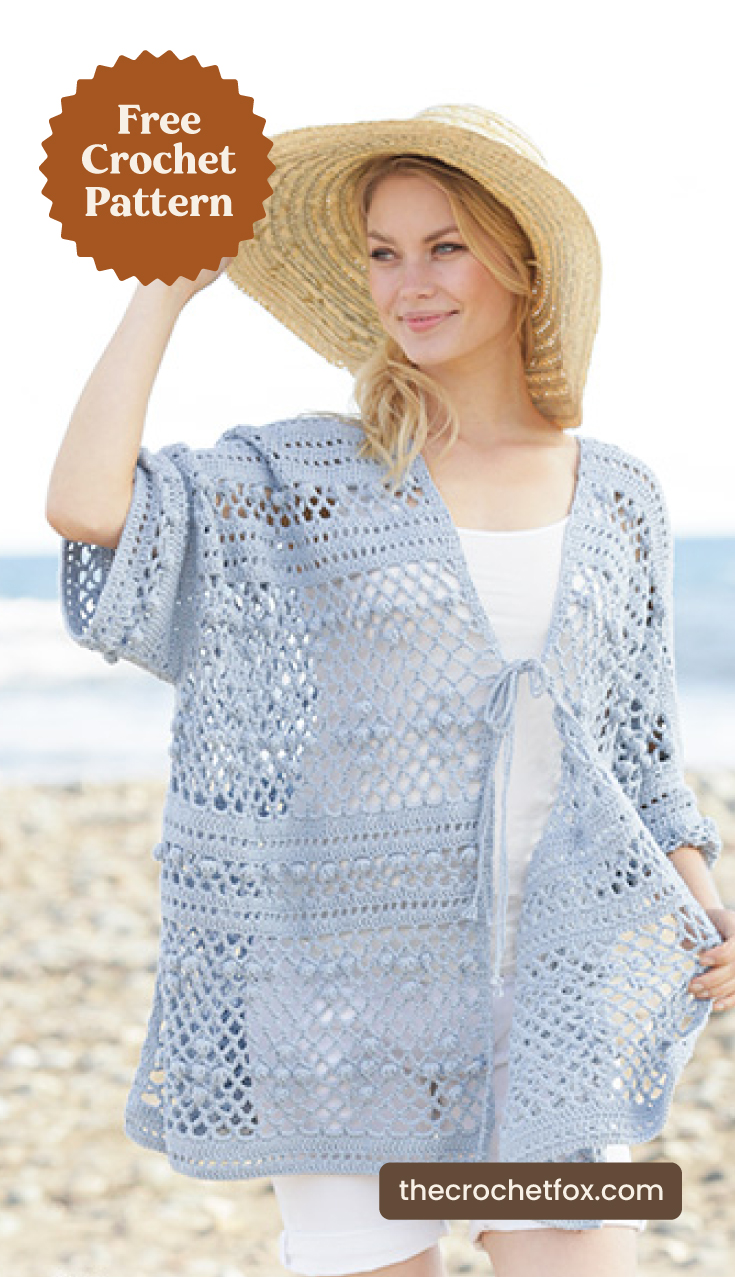 "A woman wearing a light-blue lace crochet jacket at the beach and text area which says ""Free Crochet Pattern, thecrochetfox.com"""