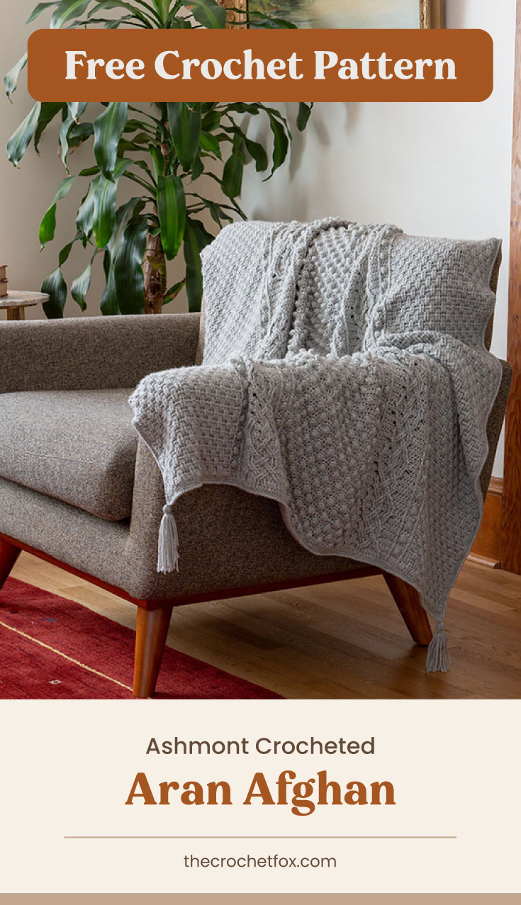 """Text area which says """"Free Crochet Pattern"""" next to a gray crocheted blanket with tassles draped over a gray couch followed by another text area which says """"Ashmont Crocheted Aran Afghan, thecrochetfox.com"""""""