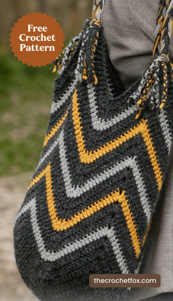 "Close-up to a gray crochet tote bag with yellow chevron stripes and text area which says ""Free Crochet Pattern, thecrochetfox.com"""