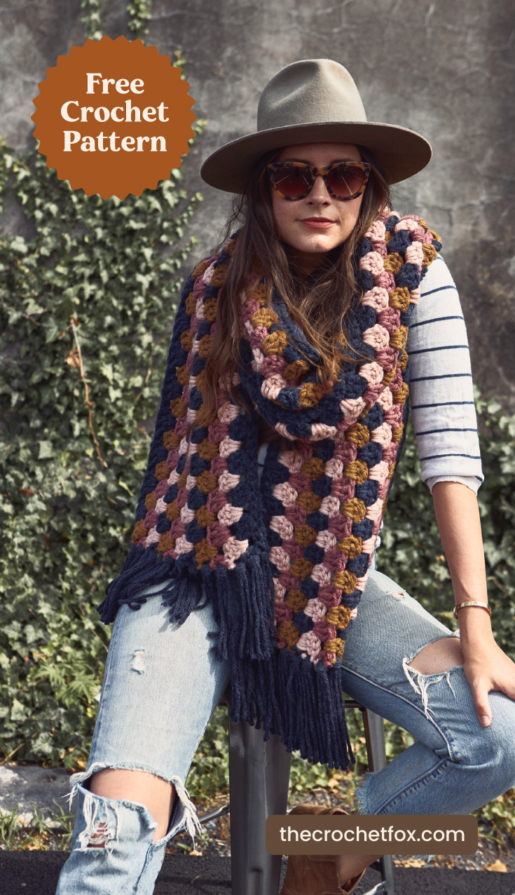 """A woman wearing a mulitcolor chunky crocheted scarf and text area which says """"Free Crochet Pattern, thecrochetfox.com"""""""