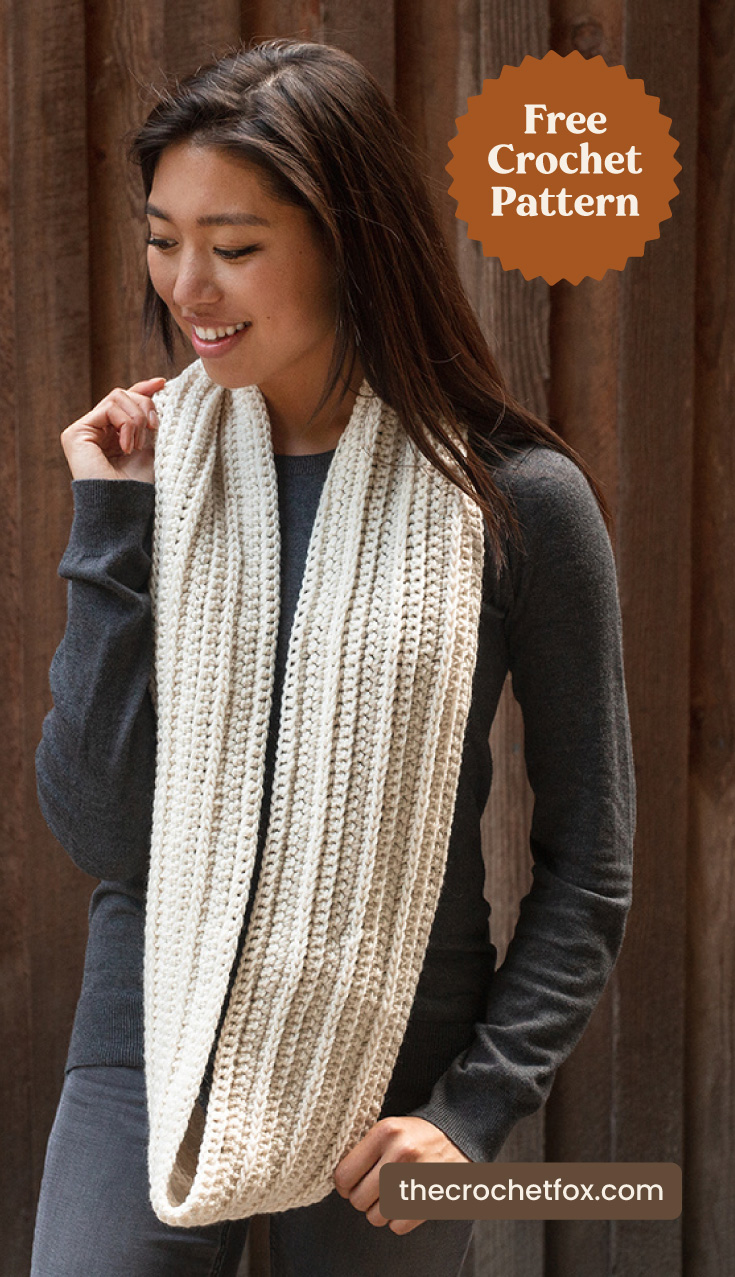 "A woman wearing a white crocheted infinity scarf and text area which says ""Free Crochet Pattern, thecrochetfox.com"""