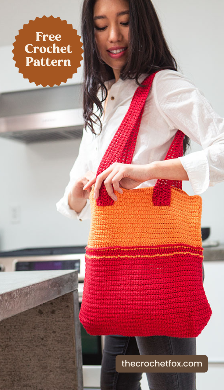 """A woman holding a red and orange crochet tote bag and text area which says """"Free Crochet Pattern, thecrochetfox.com"""""""