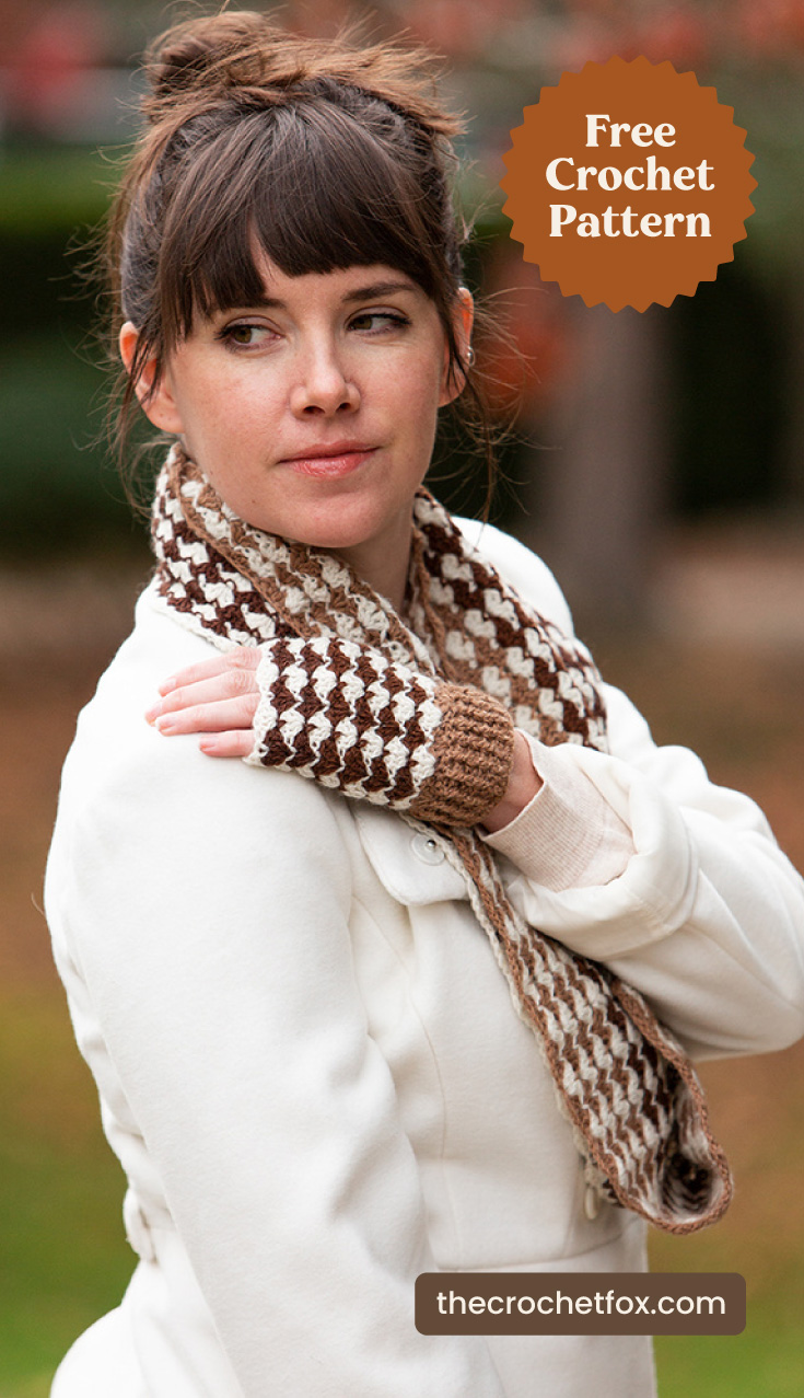 "A woman wearing a brown and white crochet cowl with a matching pair of crochet fingerless mitts and text area which says ""Free Crochet Pattern, thecrochetfox.com"""