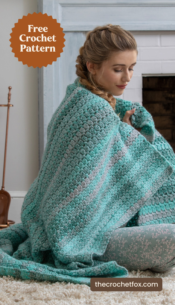"""A woman wrapped in a teal and gray crochet blanket indoors and text area which says """"Free Crochet Pattern, thecrochetfox.com"""""""
