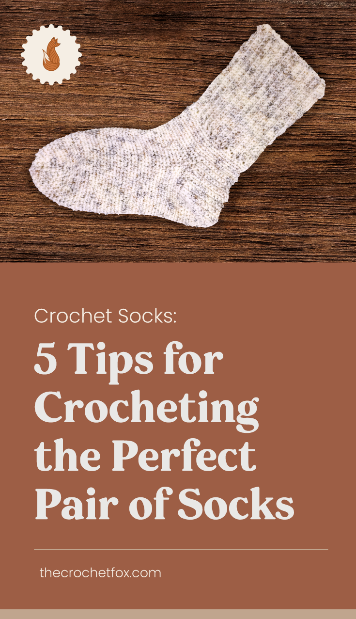 """A white crochet sock laid on a dark wooden surface next to a text area which says Crochet Socks: 5 Tips for Crocheting the Perfect Pair of Socks,thecrochetfox.com"""""""