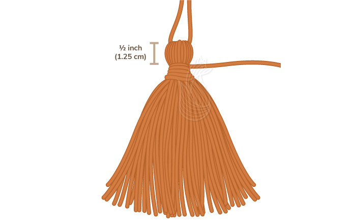 How to Make A Tassel Step 6: A orange tassel with a half inch marker to measure the top